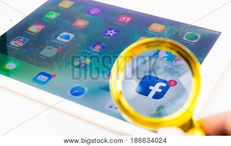 Bangkok Thailand - April 22 2017: Looking through Magnifying glass on Facebook application on iPad.