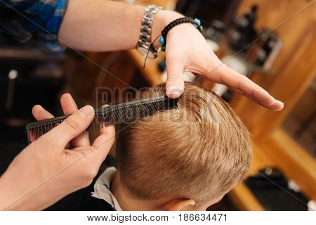 Great hairstyle. Close up of a professional comb being used by a nice male hairdresser while combing the hair of a nice young blonde boy