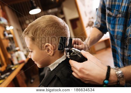 New haircut. Pleasant professional nice barber holding a comb and using a hair cutting machine while cutting the boys hair