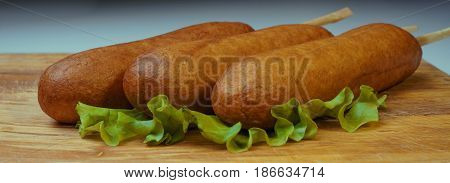 Traditional American food corn dogs on a lettuce leaf.
