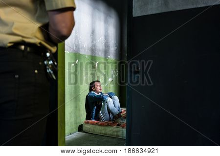 Side view of a young male prisoner thinking while sitting alone on a dirty mattress in an obsolete prison cell guarded by a police officer