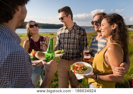 Group of friends with typical menu of summer barbecue party, burger and beer