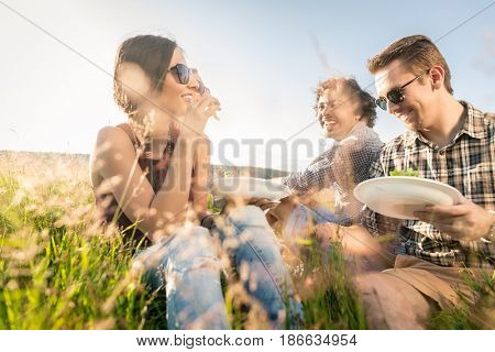 Young people having summer barbecue picnic and eating together sitting in grass