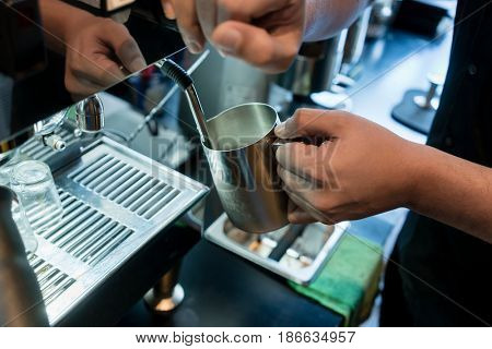 High angle view close-up of the hand of a barista holding a stainless mug while using a modern coffee machine