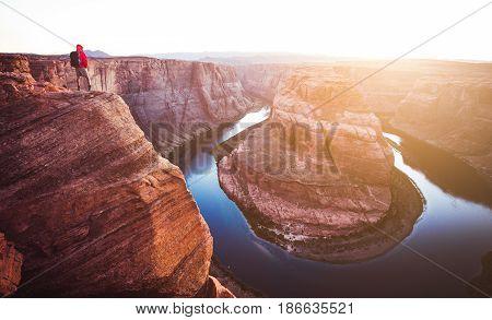 Male Hiker Overlooking Horseshoe Bend At Sunset, Arizona, Usa