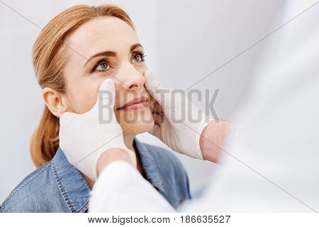 Doctors checkup. Nice pleasant attractive woman sitting in front of the doctor and looking at him while having doctors checkup