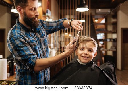 Positive mood. Cute nice young boy smiling and being in a great mood while having his hair cut
