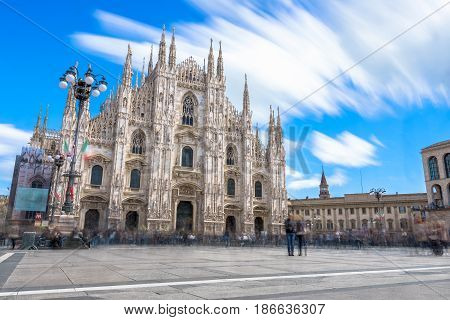 Milan Italy - April 28 2017: Daytime long exposure of front view of famous Milan gothic cathedral church (Duomo di Milano) with blue sky background in Milan Italy.