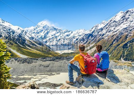 Backpackers couple hiking looking at Mt Cook view on mountains tramping in New Zealand. People hikers relaxing during hike in alps of south island.