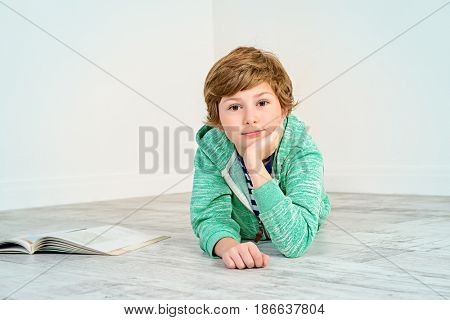 Pretty happy nine-year girl lying on a floor and smiling. Children's fashion. Education. Activity and child concept. Copy space.