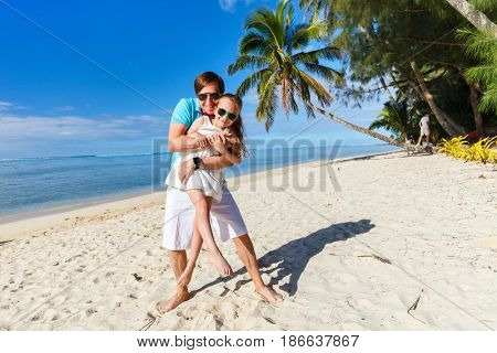 Happy father and his adorable little daughter at tropical beach during summer vacation