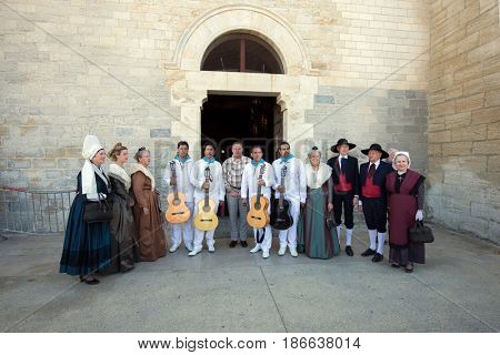 Sent-Mari-de-la-Mer, Provence, France - May 25, 2015. World Festival of Gypsies. Citizens in ancient suits and group of musicians with guitars. Entrance to the medieval cathedral Notre Dame