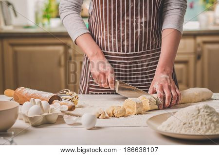 Close-up view of two woman's hands cut knife dough. A woman in a striped apron is cooking in the kitchen