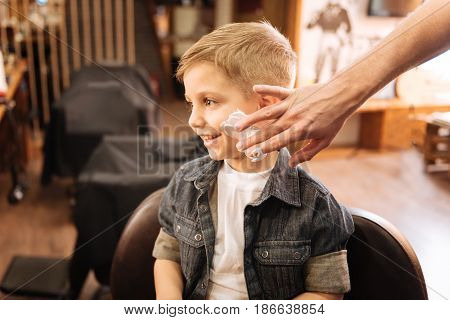 Preparation for shaving. Pleasant nice male barber having some shaving foam on his fingers and putting it on the boys cheek while preparing to shave him