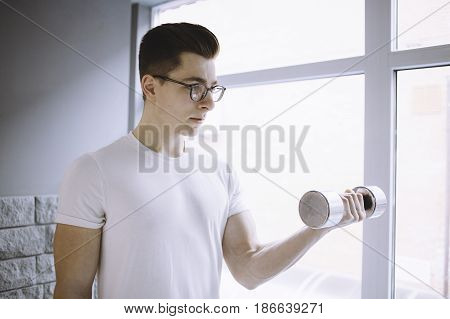 Young sportsman in white shirt with glasses doing workout with dumbbell on a white window background. He is really concentrated. Close up