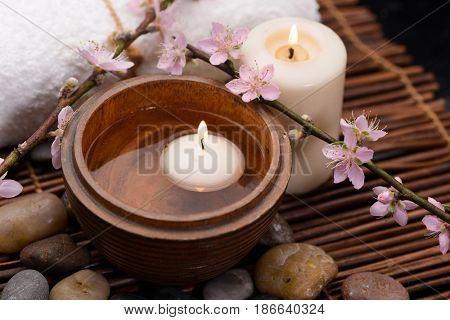 Pink cherry ,stones, candle with towel on mat background