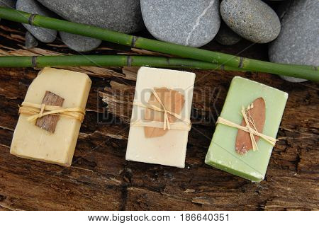 Three Soap with grove, gray stones on driftwood wood