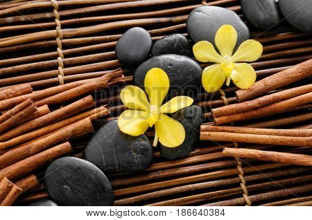 Pile of black stones with yellow orchid. cinnamon on mat