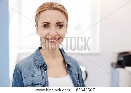 Facial surgery. Happy delighted positive woman smiling and looking at you while doing cosmetic facial surgery