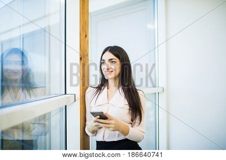 Young Woman Busy Using Her Mobile Phone While Standing In Front Of Large Glass Windows