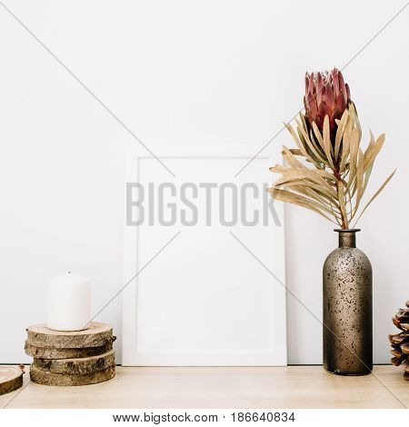 Front view blank mock up of photo frame with protea flower and trendy stuff at white background. Minimalistic decorated home office concept.