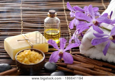 spa setting on mat background with purple orchid flower, towel