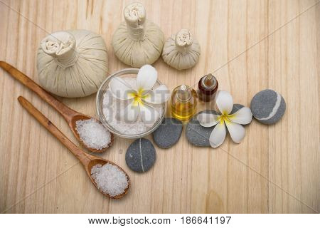 Spa treatment with spoon ,ball ,stones,oil , frangipani on wooden board background