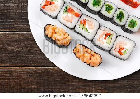 Japanese restaurant background, rolls and sushi platter closeup. Set crop, top view on rustic wood