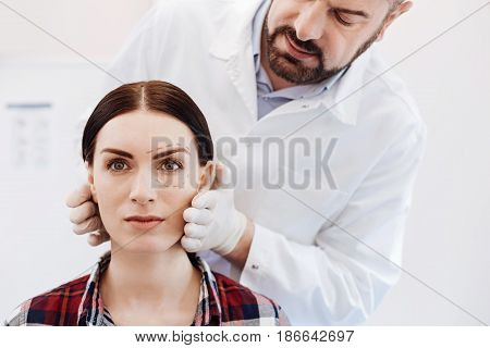 Professional cosmetic surgeon. Handsome nice bearded doctor standing behind his female patient and holding her face while preparing to cosmetic surgery