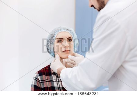I want to be beautiful. Serious young nice woman wearing a cap and sitting in front of her plastic surgeon while having an appointment with him