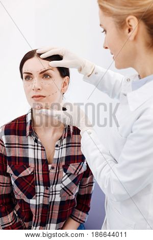 Do not worry. Delighted cosmetic surgeon holding her patients face and smiling while getting ready to a plastic surgery operation