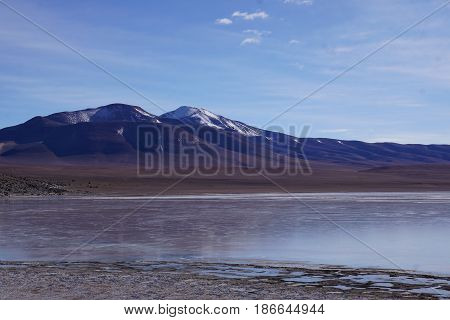 Mountain Landscape in Bolivia.  Lonely mountain in the middle of nowhere with lake in the foreground and blue skies