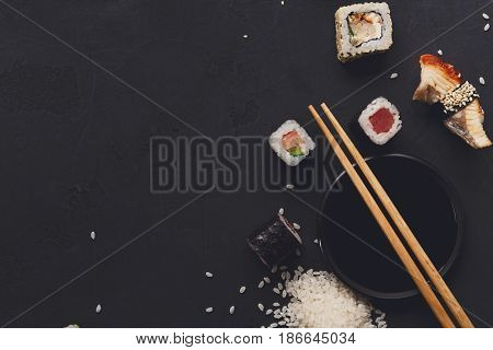 Sushi and rolls background, copy space on black, top view. Japanese restaurant food set