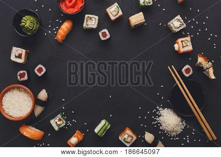 Sushi and rolls background, frame on black, top view. Colorful japanese restaurant food set