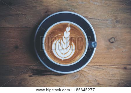 Top view image of hot latte coffee with latte art on vintage wooden table