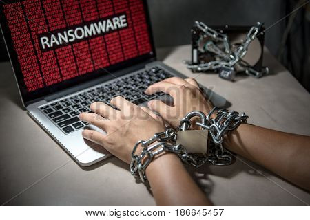 Hard disk file locked with monitor show ransomware cyber attack internet security breaches on computer laptop user hand tied up by chains and lock concept