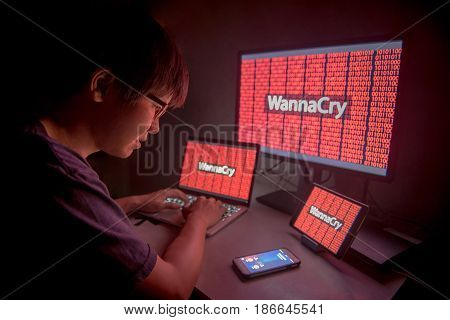 WannaCry ransomware attack on desktop screen notebook and smartphone internet cyber attack with Anonymous calling on smart phone to get the ransoms payment to decrypt the code