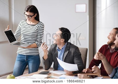 Let me say. Attractive young woman wearing striped jumper holding laptop on both hands while looking at screen
