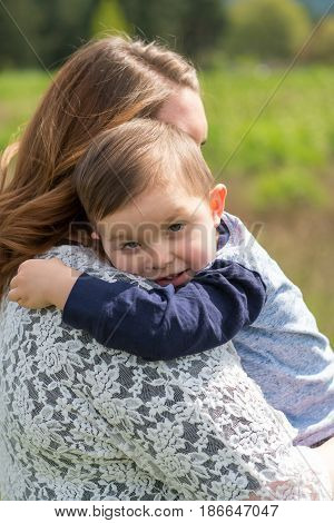 Realistic lifestyle portrait of a mother and her son together outdoors in a natural field in Oregon.