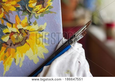Artist's workshop. Canvas, paint, brushes, palette knife lying on the table
