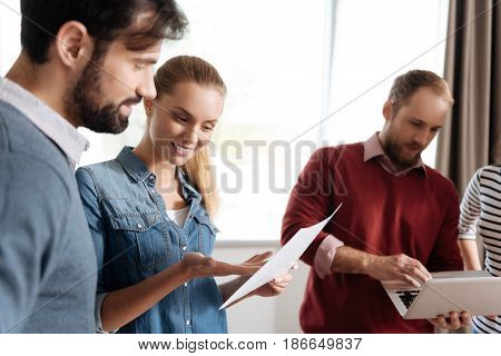 Just imagine. Pretty woman standing in semi position keeping smile on face while showing sheet of paper