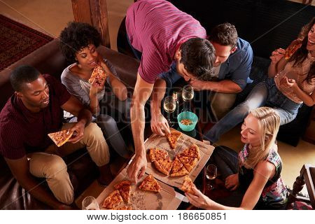 Young adults eating pizzas at a party at home, elevated view