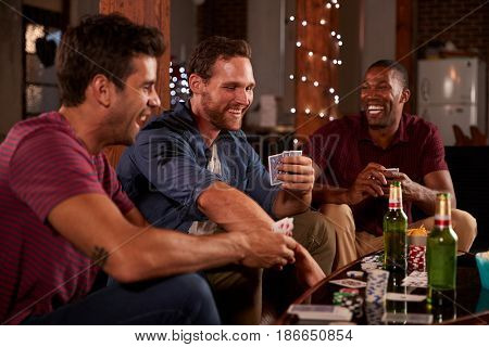 Three male friends playing cards and laughing at home