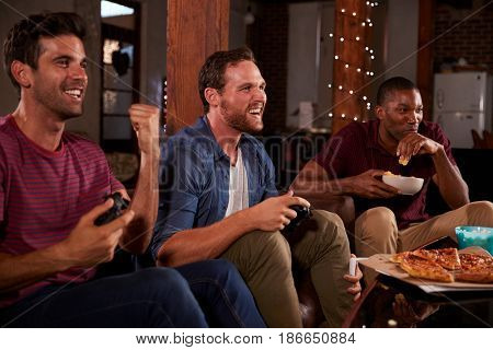 Three male friends playing video games and eating at home