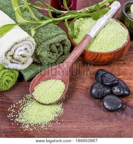 green Spa tools with candle and towel on wood