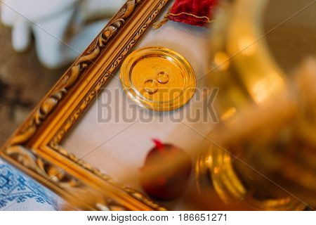 Two golden wedding rings in ceremonial bown on church altar with carving.