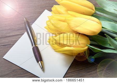 bunch of yellow tulips and postcard on wood