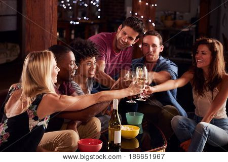 Young adult friends having a party at home making a toast