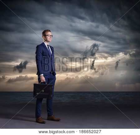 Businessman with briefcase standing on a dark, dramatic ocean background. Business concept.