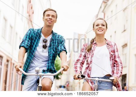 Happy traveling couple riding on bicycles. Boyfriend and girlfriend in old town. Love, relationship, romance concept.